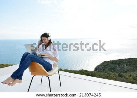 beautiful young woman relax and work on laptop computer while working on laptop computer and read book at home