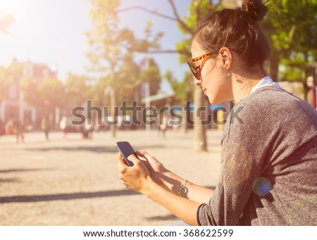 Beautiful young woman relax in Vondelpark Amsterdam smartphone in hands , enjoying the internet outside - stock photo