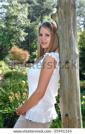 Beautiful young woman relaxes in the Birmingham Botanical Garden in Birmingham, Alabama.  She is relaxing against a rustic wooden pole. - stock photo
