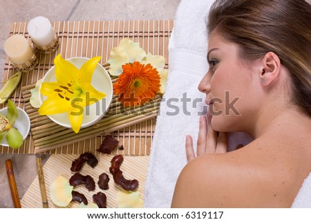 Beautiful young woman  relaxin in spa salon with flowers and candles