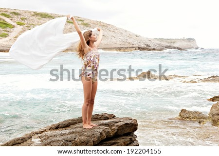 Beautiful young woman relaxing and enjoying a summer holiday, sitting on a rock platform on the shore of a beach and covering herself in a white fabric sarong during a breezy day. Outdoors lifestyle. - stock photo