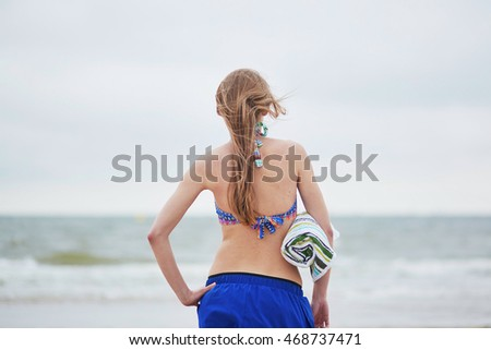 Beautiful young woman relaxing and sunbathing on sand beach
