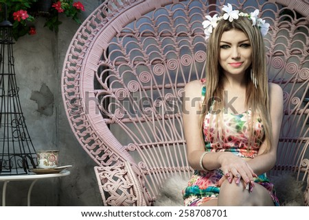 Beautiful Young Woman Relaxing At Pink Chair In The Garden And Drinking A Cup Of Coffee - stock photo