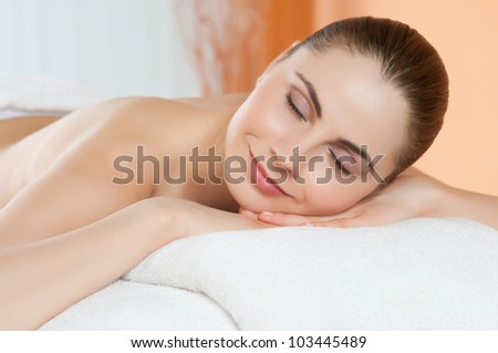 Beautiful young woman relaxing at spa - stock photo