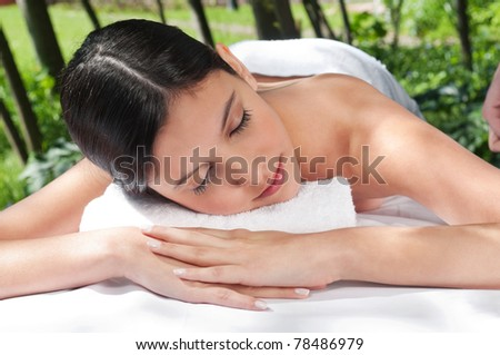 Beautiful young woman relaxing at spa in a natural setting - stock photo