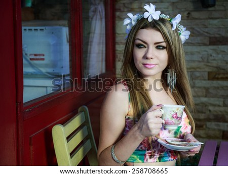 Beautiful Young Woman Relaxing At Table In The Garden Drinking A Cup Of Coffee - stock photo