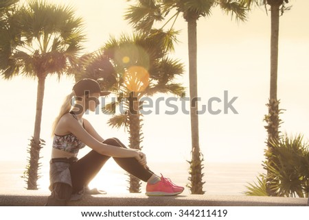 Beautiful young woman relaxing close to the sea after the hard workout and watching sunset. Golden colors made nice feeling and matching with long blonde hair of the girl.  - stock photo