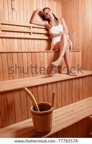 Beautiful young woman relaxing in a finish sauna - stock photo