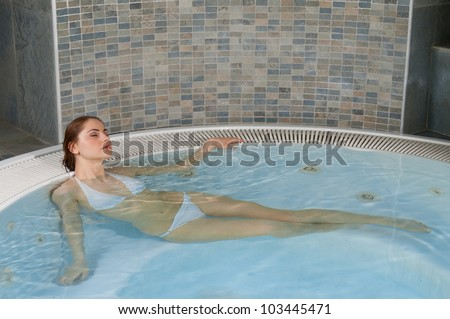 Beautiful young woman relaxing in a jacuzzi hot tub at spa