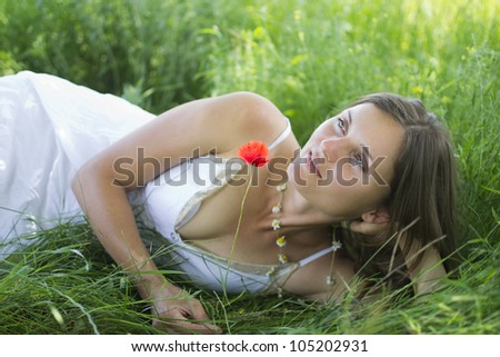 Beautiful young woman relaxing in a meadow, holding a poppy - stock photo
