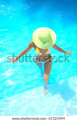 Beautiful young woman relaxing in a swimming pool in Greece - stock photo