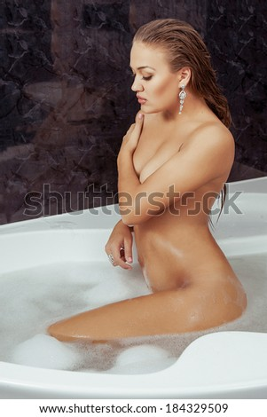 beautiful young woman relaxing in bubble bath - stock photo