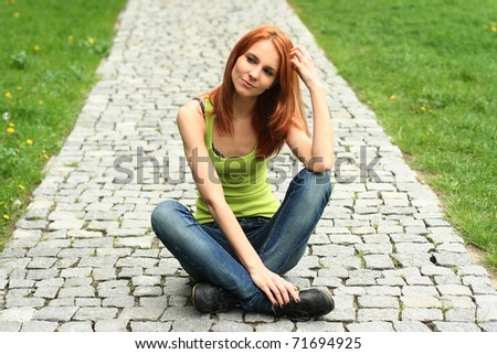beautiful young woman relaxing in park - stock photo
