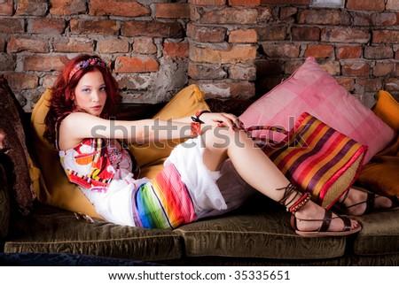 beautiful young woman relaxing in sofa - stock photo