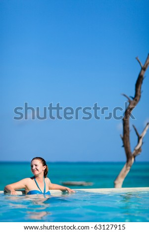 Beautiful young woman relaxing in swimming pool - stock photo