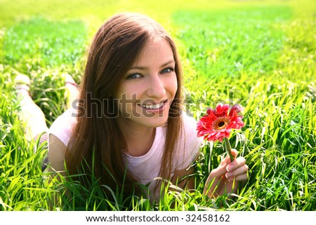beautiful young woman relaxing in the grass - stock photo