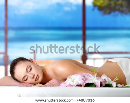 Beautiful young woman relaxing in the spa  salon in a resort - nature background - stock photo