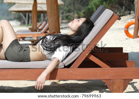 beautiful young woman relaxing near the ocean and taking sunbath - stock photo