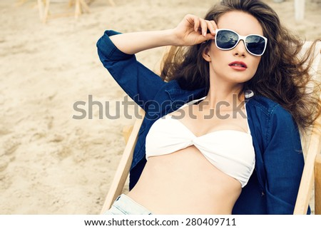 beautiful young woman relaxing on a deckchair at the beach. Sunbathing - stock photo