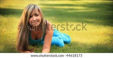 beautiful young woman relaxing on a grass
