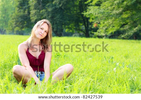 Beautiful young woman relaxing on green grass. Summertime