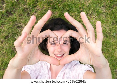 beautiful young woman relaxing on green grass with hands in hearth symbol - stock photo
