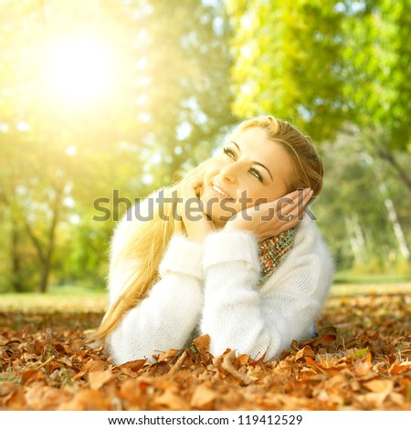 Beautiful young woman relaxing on leaves in the park. - stock photo