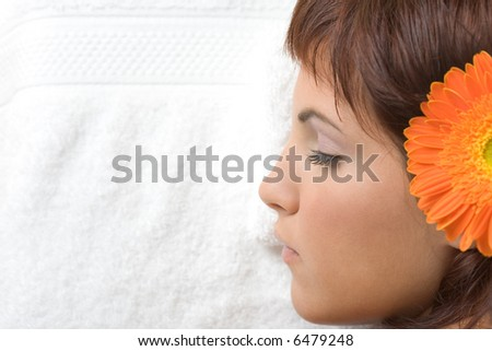 Beautiful young woman relaxing on massage table with a flower in her head - Beauty and Spa - stock photo
