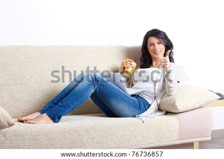 Beautiful young woman relaxing on sofa with laptop and a cup of tea showing thumb up in home - stock photo