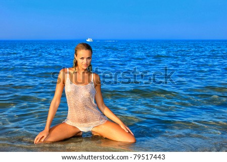 Beautiful young woman relaxing on the beach in Greece - stock photo