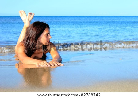 Beautiful young woman relaxing on the beach in Greece