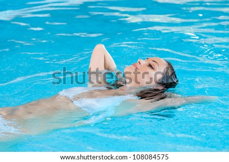Beautiful young woman relaxing on water at swimming pool - stock photo