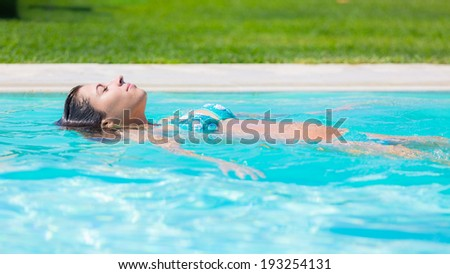 Beautiful Young Woman Relaxing on Water Surface - stock photo