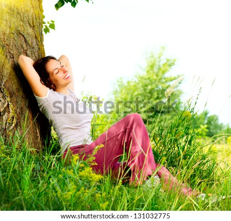 Beautiful Young Woman Relaxing Outdoors. Meadow. Beauty Girl Enjoying Nature - stock photo