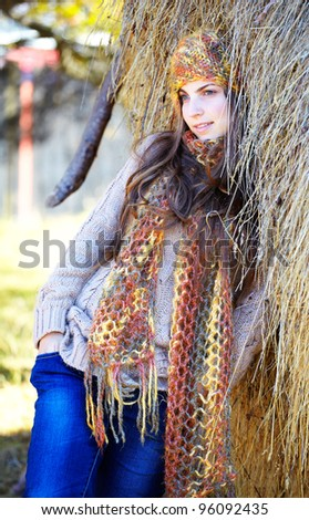 Beautiful young woman relaxing under a hay stack in autumn. - stock photo