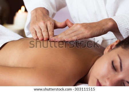 Beautiful young woman relaxing with hand massage at beauty spa. Close-up - stock photo