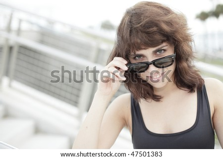 Beautiful young woman removing her sunglasses and smiling