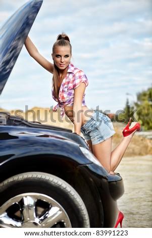 beautiful young woman repairing the car - stock photo