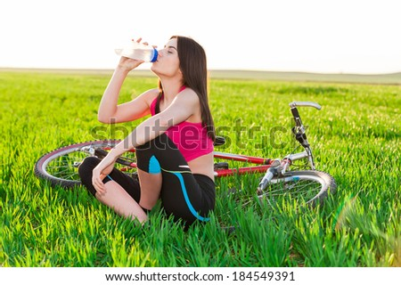 Beautiful young woman resting and enjoying a bottle of water outdoors and the bike on background - stock photo