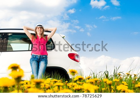 Beautiful young woman resting at side of her car at flower field with blue cloudy sky in background - stock photo