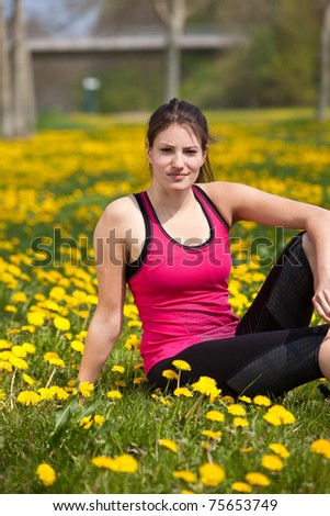 Beautiful young woman resting in a field with dandelions - stock photo