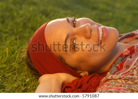 Beautiful young woman resting on the grass outside during the perfect golden hour - stock photo