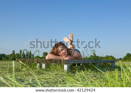 Beautiful young woman rests on the green grass - stock photo