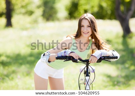 beautiful young woman  riding a bicycle on a warm summer day