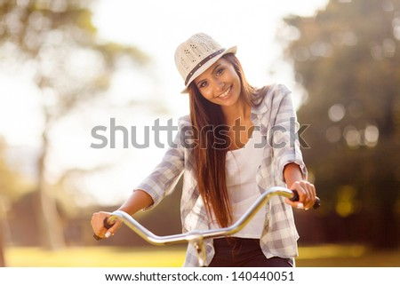 beautiful young woman riding a bicycle outdoors - stock photo