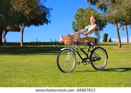 Beautiful young woman riding a classic bicycle.