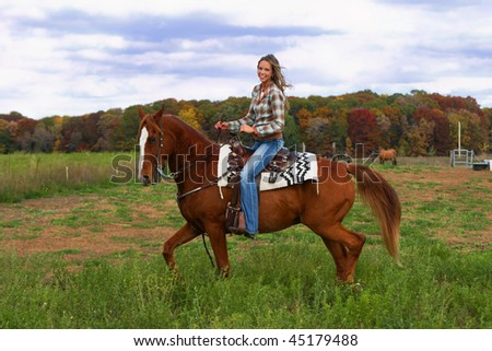 Beautiful young woman riding a handsome horse. - stock photo