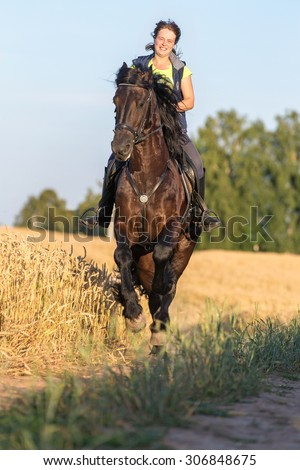 Beautiful young woman riding a horse. - stock photo