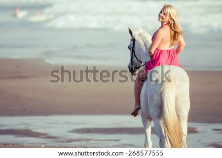 Beautiful young woman riding a horse along the beach, she is happy of her hobby - stock photo