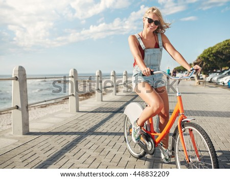 Beautiful young woman riding bicycle at the waterfront. Stylish young female cycling on a seaside promenade on a summer day. - stock photo